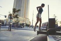 Молодая женщина, осуществляющая на открытом воздухе, поднявшись на скамейку — стоковое фото