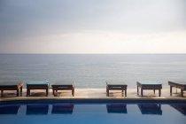 Шезлонги біля басейну з видом на океан — стокове фото