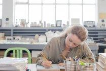 Female print designer working on sketchbook in workshop — Stock Photo