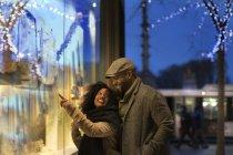 Romantic happy couple enjoying city during winter holidays window shopping — Stock Photo