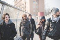 Cinque giovani amici adulti passeggiando sul ponte pedonale — Foto stock