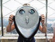 Vista frontale della giovane donna che guarda attraverso il binocolo — Foto stock
