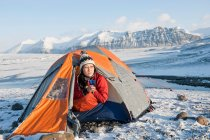 Hiker drinking in camping tent in snow — Stock Photo