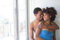 Ritratto di giovane coppia alla finestra, uomo con braccio intorno alla donna — Foto stock