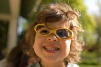 Young girl wearing broken sunglasses — Stock Photo