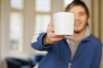 Mann bietet Kaffeetasse an — Stockfoto
