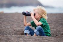 Menino usando binóculos na praia — Fotografia de Stock