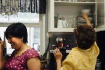 Женщина на кухне кладет посуду в кухонный шкаф — стоковое фото