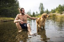 Young man sitting in river petting dog, Lake Tahoe, Nevada, USA — Stock Photo