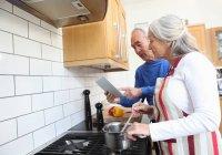 Vieux couple cuisine ensemble dans la cuisine — Photo de stock