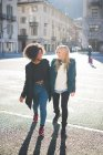 Two female friends talking and strolling in town square — Stock Photo