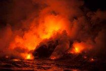 Fumer des nuages de coulée de lave ayant une incidence sur la mer dans la nuit, du volcan Kilauea, Hawaii — Photo de stock