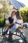 Fille assise sur les genoux de mère sur une chaise longue sur la terrasse en bois — Photo de stock