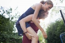 Дівчинка-підліток даючи кращий друг скарбничку назад в парку — стокове фото