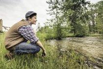 Vista lateral do menino adolescente vestindo tampa plana agachado na margem do rio olhando para longe sorrindo — Fotografia de Stock