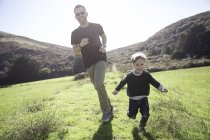 Pai e filho correndo ao ar livre — Fotografia de Stock