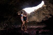Friends in cave wearing swimwear, Oahu, Hawaii, USA — Stock Photo