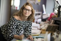 Female print designer drawing designs in workshop — Stock Photo