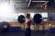 Woman lifting barbell on shoulders in gym — Stockfoto
