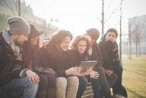 Sechs junge Erwachsene Freunde lesen digital-Tablette auf Parkbank — Stockfoto