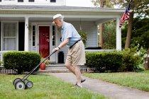 Старший мужчина, косить лужайку перед его — стоковое фото