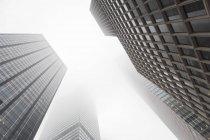 Blick von unten auf Wolkenkratzer im Nebel, schwarz-weiß — Stockfoto