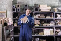 Worker inspecting part of mould in foundry — Stock Photo