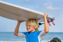 Jovem na praia, carregando prancha na cabeça — Fotografia de Stock