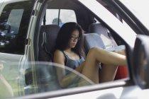 Ritratto di giovane ragazza in pick up camion guardando smartphone — Foto stock
