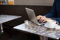Empresario que utiliza el ordenador portátil en la mesa de café - foto de stock