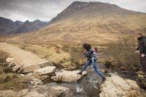 Woman leaping over stream, Fairy Pools, near Glenbrittle, Isle of Skye, Hebrides, Scotland — Stock Photo