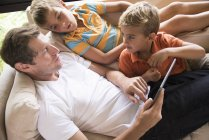 Man and two sons using digital tablet touchscreen on sofa — стокове фото