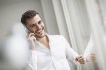 Jeune homme d'affaires riant tout en bavardant sur smartphone au bureau — Photo de stock