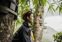 Young man by tree wearing climbing helmet and looking away, Ban Nongluang, Champassak province, Paksong, Laos — Stock Photo