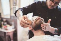 Barba da barbiere spazzolatura cliente nel negozio di barbiere — Foto stock