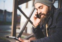 Hombre adulto medio, sentado al aire libre, uso de teléfono móvil y tableta digital - foto de stock