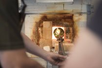 Glassblower heating formed glass in furnace — Stock Photo