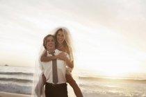 Наречена їзда piggyback на нареченого на пляжі проти заходу сонця — стокове фото