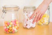 Female hand touching jar of marshmallows — Stock Photo