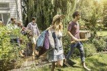 Amigos masculinos e femininos caminhando no jardim se preparando para piquenique — Fotografia de Stock