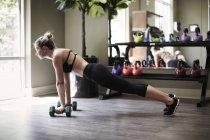 Mulher malhando com halteres no ginásio — Fotografia de Stock