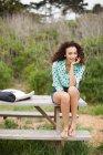 Молодая женщина сидит на столе для пикника улыбаясь, портрет — стоковое фото