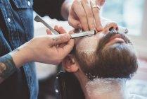 Парикмахер бритья клиента лицо с бритвой — стоковое фото
