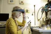 Female jewellery maker looking at smartphone in design studio — Stock Photo