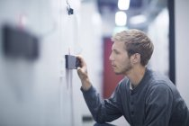 Male technician crouching to turn switch in technical room — Stockfoto