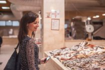 Woman looking at fresh fish in market — Stock Photo