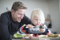 Father and son preparing food together at home — Stock Photo