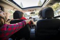 Drei Freunde im fahrenden Auto, zwei Freunde teilen Chips — Stockfoto
