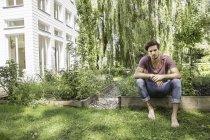 Junger Mann sitzt im Garten — Stockfoto