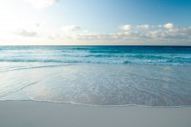 Vagues de surf sur la plage de sable sous le ciel nuageux — Photo de stock